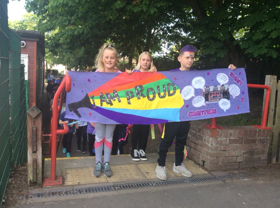 Photo of students holding a 'I Am Proud' banner