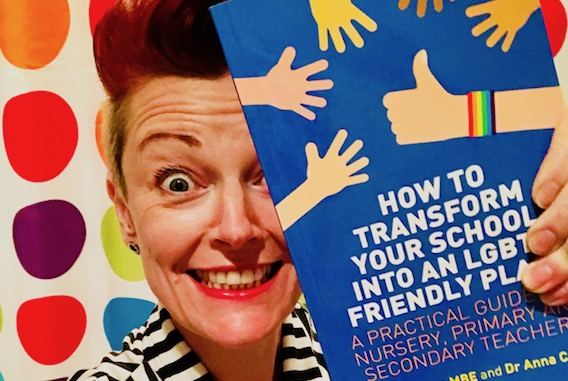 Elly Barnes holding How to transform your school into an LGBT+ friendly place book